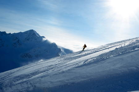 Skier going down the slope on a background of blue sky and mountains Stock Photo