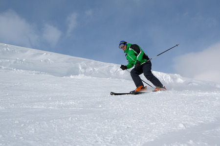 Skier going down the snowy slope, lower point shooting Stock Photo