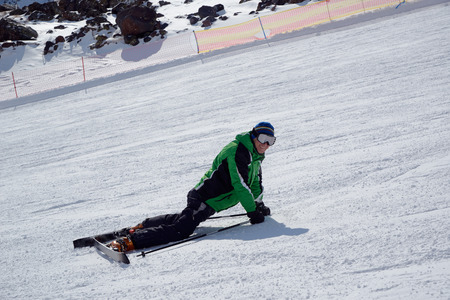 Smiling skier lying with skis on ski slope