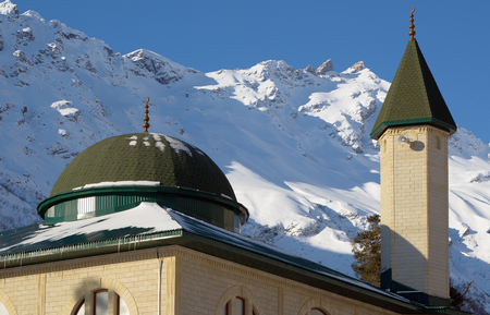 Minaret and roof of the mosque on the background of snow-capped mountains