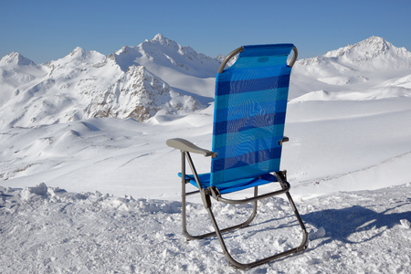 Empty blue chaise lounge, facing the snow-covered mountains