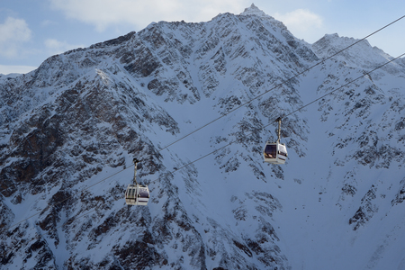 Mountain lift against snowy mountain peaks Stock Photo