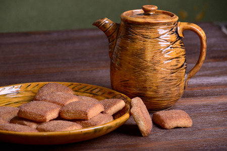 Cookies with cinnamon on a platter and teapot on a wooden board