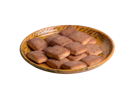 A cookie with cinnamon lies on a golden plate, isolated on white