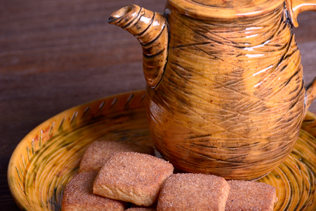 Cookies with cinnamon on a platter and teapot close up Stock Photo