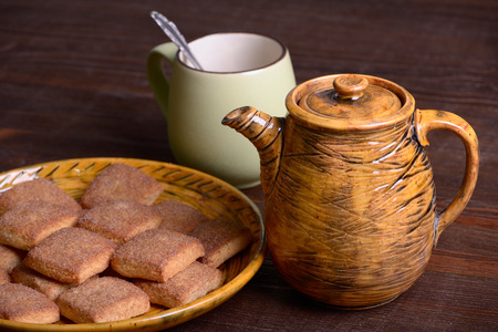 Teapot and cookies with cinnamon on a platter on a wooden board