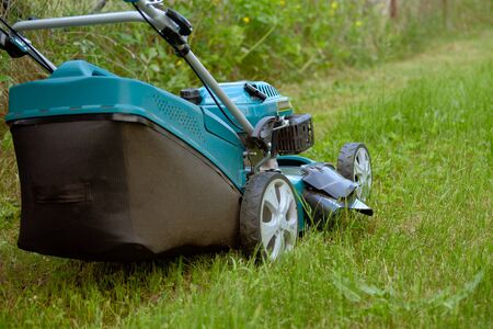 Lawn mower cutting green grass in backyard close up.