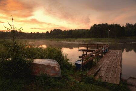 Summer sunset on a forested river with inverted boats and a old wooden pier 版權商用圖片