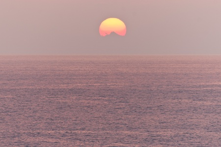 Pink ocean sunset with funny shadow on the sun. Stock Photo - 11790683