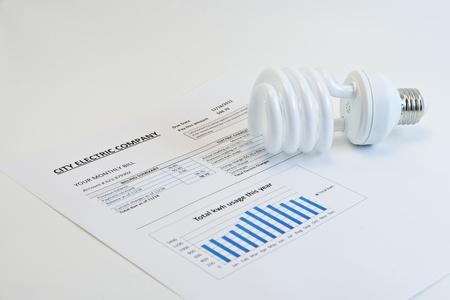 Energy efficient CFL bulb on electric bill on light background photo