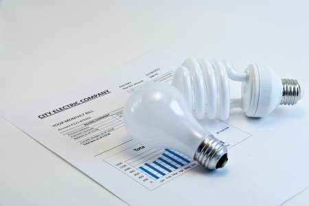 helical: Energy efficient and incandescent  bulbs on electric bill on light background