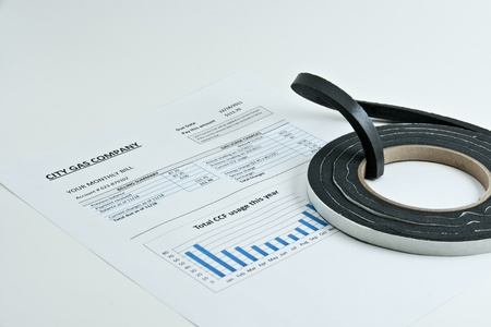 conserving: Insulation weather strip on heating gas bill on light background.