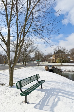 Winter city scene with a bench near pond  at neighborhood recreation area  photo