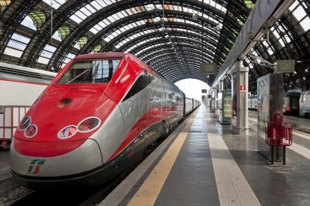 밀라노, 이탈리아 - 2012년 4월 21일 : 밀라노 센트 랄 역에서 Freccia 로사 고속 열차. 밀라노 센트 랄은 원래 1864 년에 지어진 유럽에서 가장 아름다운 기차
