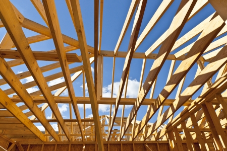 attic: Home construction with wood framing and roof trusses against a blue sky