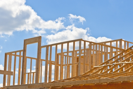 housebuilding: New residential construction home framing against a blue sky  Door to your dream