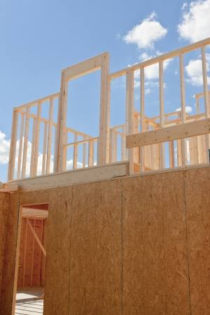 attic: New residential construction home framing against a blue sky  Door to your dream