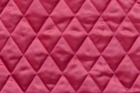 Close up of quilted christmas tree skirt fabric in traditional red color