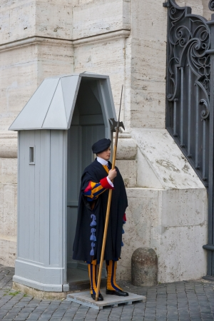 VATICAN CITY, ITALY - APRIL 24, 2012: A Papal Swiss Guard standing with a halberd circa in traditional uniform on April 24, 2012. Vatican City State is a sovereign city-state within the city of Rome.