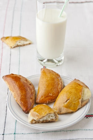 Homemade pastry filled with ricotta cheese - called sochniki in Russian cuisine, and glass of milk  selective focus Stock Photo