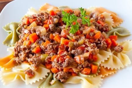 Three colors farfalle pasta with bolognaise sauce Фото со стока