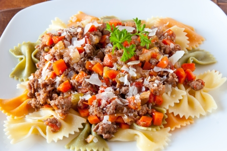 Three colors farfalle pasta with bolognaise sauce garnished with   shaved parmesan cheese