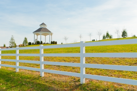 Gazebo in the new city park behind white fence at autumn photo