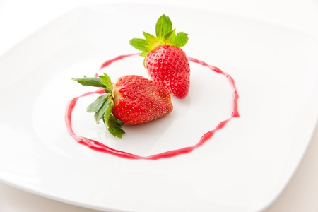 Fresh strawberries  as romantic dessert  on a plate in heart shape of berry sauce  selective focus