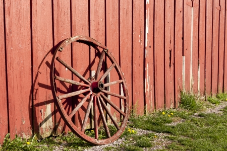 Old rustic wagon wheel beside a red barn  photo