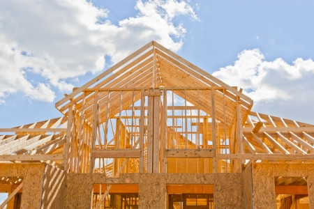 wooden beams: New residential construction home framing against a blue sky