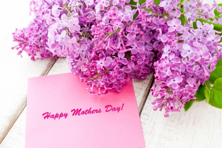 Lilac bouquet with Happy Mothers Day card  on wooden table photo