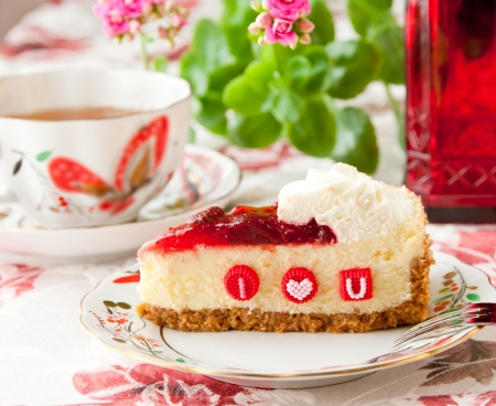 Piece of strawberry cheesecake with edible letters for Valentines day  selective focus Stockfoto