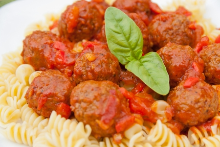 Meatballs with homemade tomato sauce and pasta rotini  selective focus photo