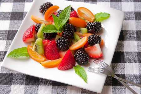 Fruit salad with fresh strawberries, blackberries,  kiwis and  kumquats on white plate  Healthy eating, berry dessert  selective focus  photo
