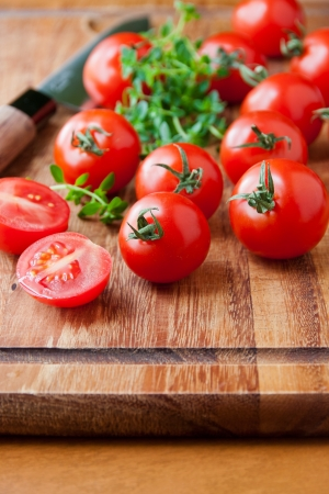Tomatoes, thyme herb and knife on wooden cutting board  selective focus, shallow dof photo
