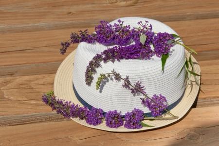 Butterfly bush blossom on summer hat at garden  Summertime concept  photo