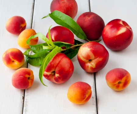 Colorful summer fruits - apricots, nectarines and peaches on wooden table. photo