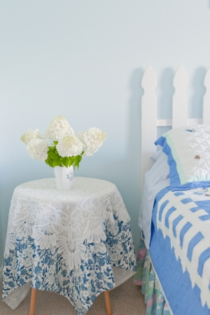 Bouquet of white hydrangea flowers on a side bed table in a country bedroom  photo
