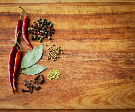 Dried red chili peppers and spices on rustic, dark wood cutting board. Low key still life.