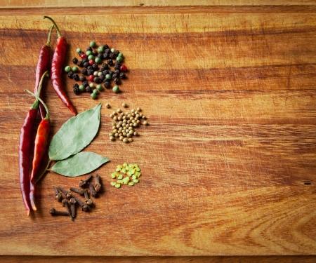 legumbres secas: Secos chiles rojos y especias en r�stico, tabla de cortar de madera oscura. Baja clave sigue la vida.