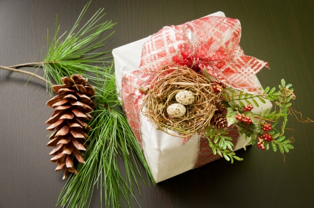 Christmas gift box in silver with red bow and bird nest decoration, near pine winter greenery with cone on wooden table. photo