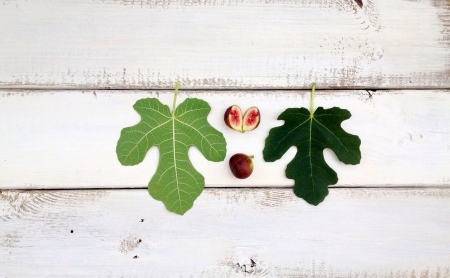 Figs fruits and leaves on wooden board