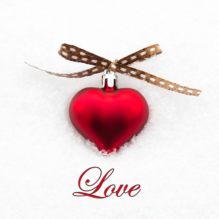 Love greeting card with red heart on the snow photo
