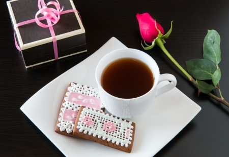 Cup of tea with homemade gingerbread cookies, red rose and a gift box  photo