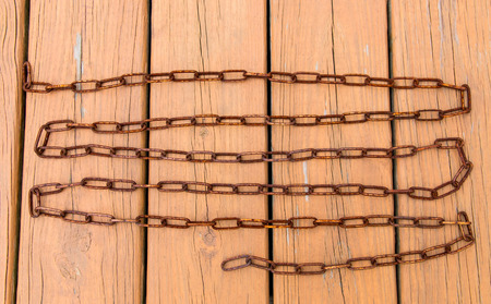 rusty chain: Old rusty chain on wooden floor