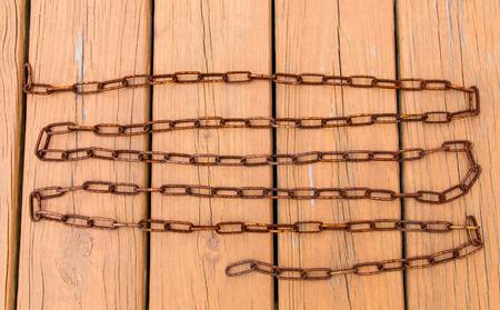 Old rusty chain on wooden floor photo