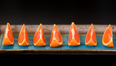 Slices of  the cara cara oranges with its pinkish red color interior on a plate  selective focus