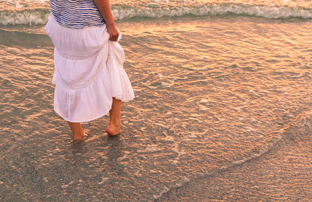 Body part outdoor portrait of a woman  in white cotton skirt walking along coastal line.