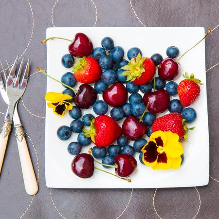 Plate of summer   berries -  blueberries, strawberries, and cherries. 版權商用圖片