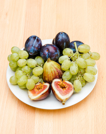 Fruits plate with plums, figs and white grapes. photo